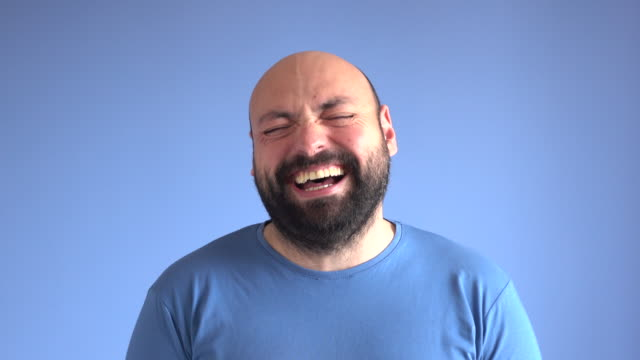 uhd video portrait of laughing adult man - ridere video stock e b–roll