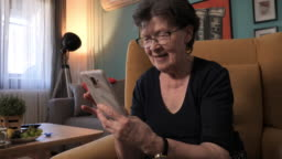 Video portrait of senior woman at home using smart phone and watching images or movies