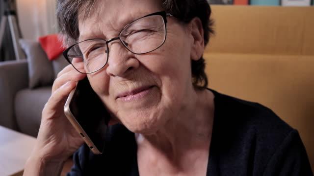 vídeos de stock e filmes b-roll de video portrait of senior woman at home using smart phone - 70 anos