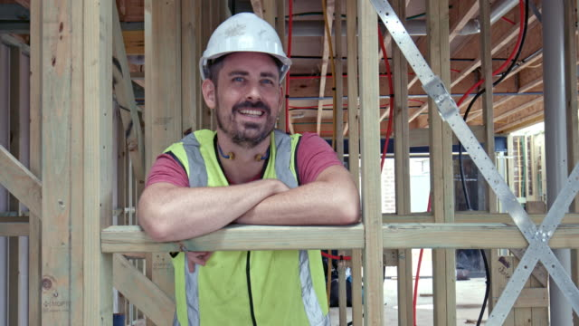 video portrait of smiling construction worker at site - protective workwear stock videos & royalty-free footage