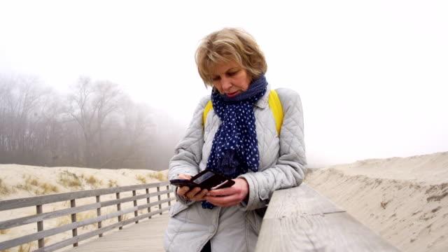 vídeos y material grabado en eventos de stock de vídeo retrato de la mujer mayor atractivo de 50 años de edad hablando a través de teléfono móvil en la playa de invierno - 50 54 years