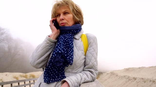 video-portrait der 50 jahre alte attraktive senior frau sprechen über handy am strand im winter - 50 54 years stock-videos und b-roll-filmmaterial