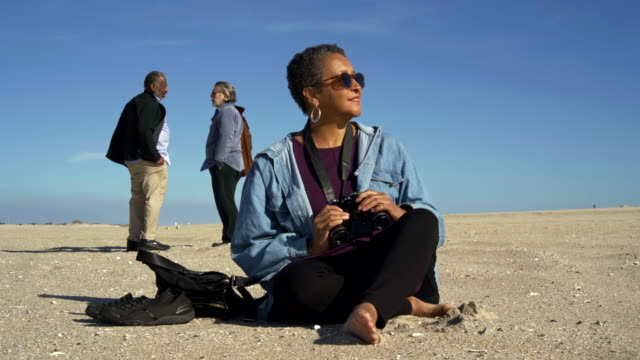 Video Portrait of the attractive senior African-American woman who sitting on the sand on the beach in front of the group of friends
