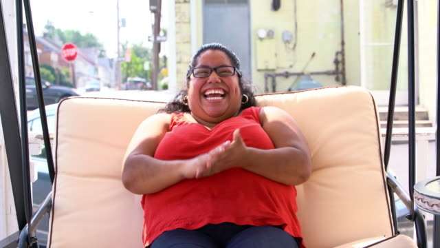video portrait of the body-positive, optimistic pretty latino - mexican woman swinging on the swings at the porch. - body positive stock videos and b-roll footage