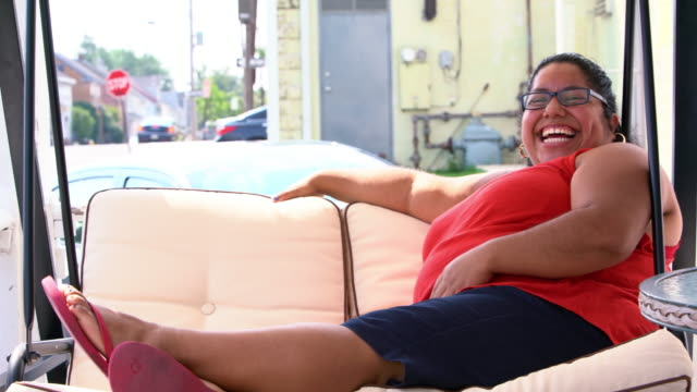 vídeos de stock, filmes e b-roll de retrato de vídeo o corpo positivo, otimista latino bonito - mulher mexicana balançando no balanço na varanda. - body positive