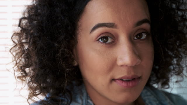 video portrait of the young black, mixed-race woman in her apartment. closeup shot with approaching camera motion. - video portrait stock videos & royalty-free footage