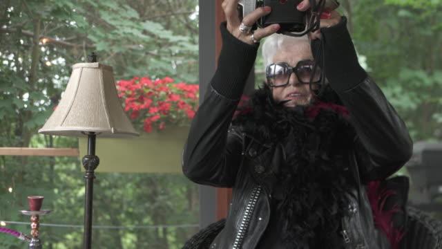 stockvideo's en b-roll-footage met video portret senior woman alleen het nemen van selfie - excentriek
