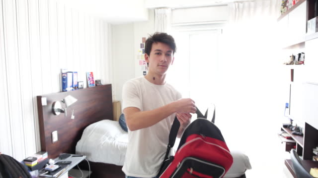 video portrait teenage boy picks up satchel standing in his bedroom - satchel stock videos & royalty-free footage