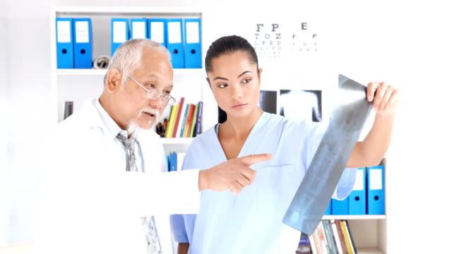 4K Video Senior Arzt erklären, Röntgenbild, Student der Medizin