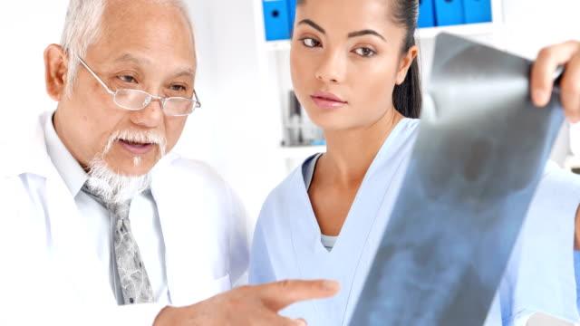 4K Video Senior doctor explaining x-ray image to medical student