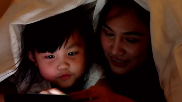 video series of asian family , happy mother and daughter relax at home watching movie in bed room . - daughter stock videos & royalty-free footage