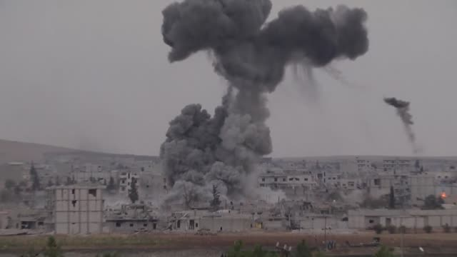 a video shot from sanliurfa turkey shows smoke rising from an explosion in the syrian border town of kobani following a usled coalition airstrike... - luftangriff stock-videos und b-roll-filmmaterial
