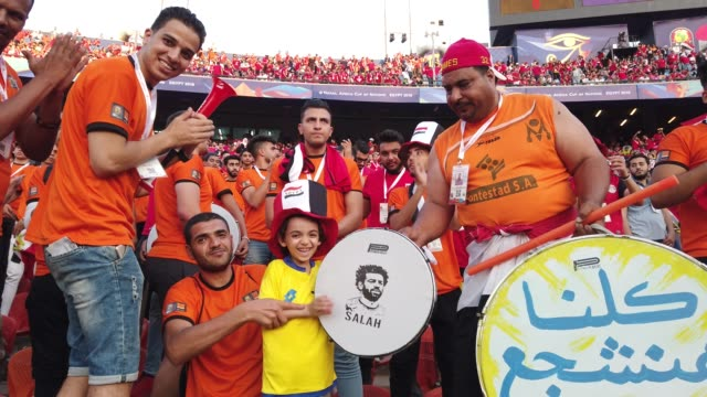 video shows egypt fans including a very young fan with a mohamed salah branded drum banging drums singing blowing horns before the afcon 2019 group a... - atmosfär råmaterial bildbanksvideor och videomaterial från bakom kulisserna