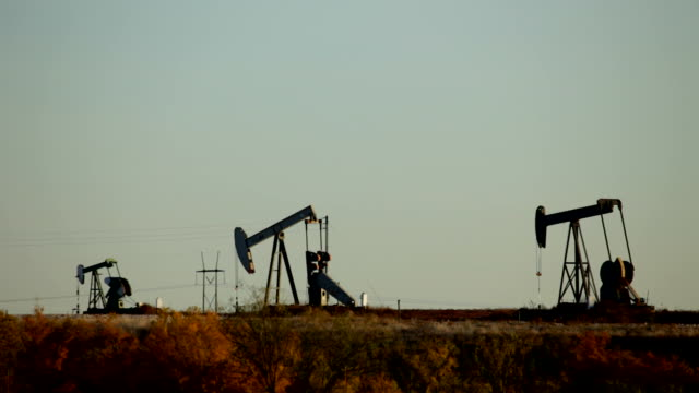 hd video silhouetted oil rigs pump in texas fields - oljepump bildbanksvideor och videomaterial från bakom kulisserna