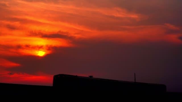 vidéos et rushes de 4 k vidéo: sky train fonctionnant sur les rails de chemin de fer au coucher du soleil au coucher du soleil. - crépuscule