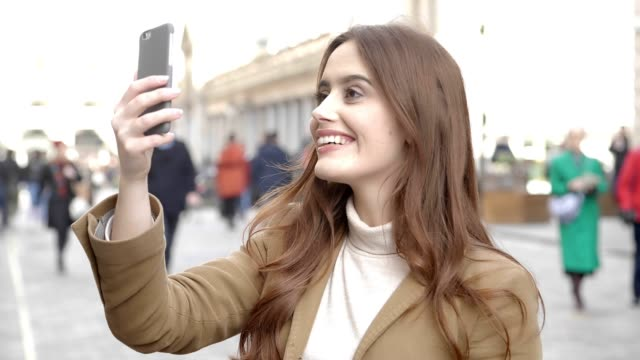Video smartphone call in the city. Happy young woman.