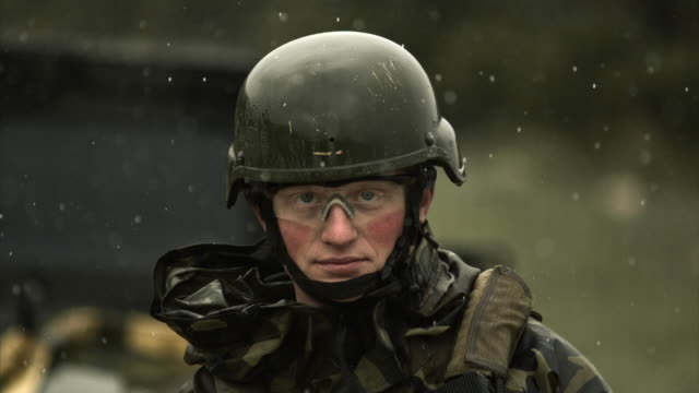 Video speeds change while soldier look at the camera, in the rain.