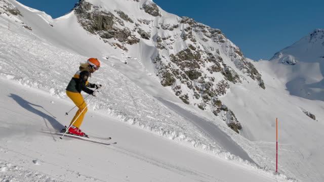 4k video sporty woman skiing in short turns - sci e snowboard video stock e b–roll