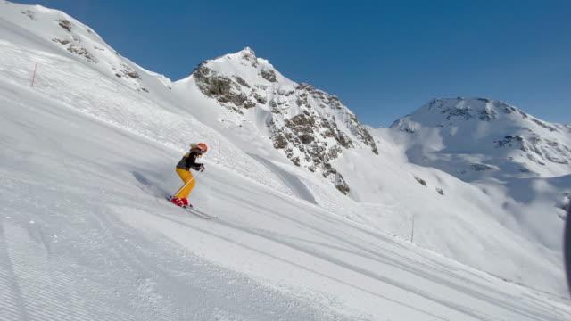 4k video tracking woman skiing on ski slope - sci e snowboard video stock e b–roll