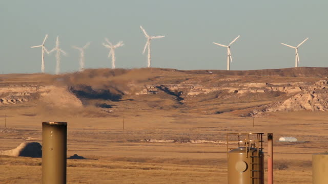 HD video wind farm and oil well flares Colorado grasslands