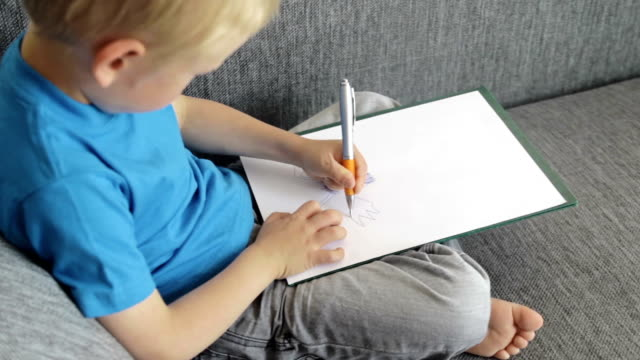 Video with boy drawing something