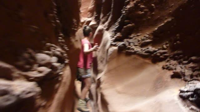 hd video woman hiking sandstone slot canyons escalante utah - slot canyon stock videos and b-roll footage