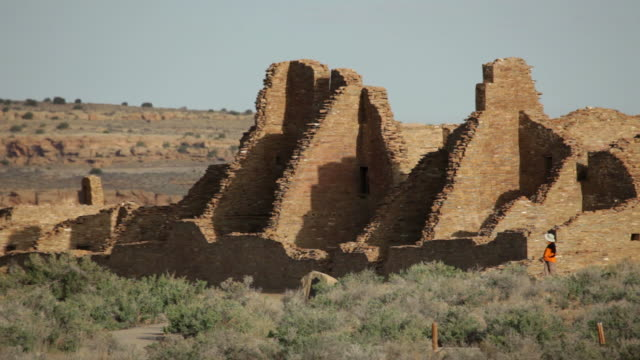 HD video woman looks at pueblo ruin Chaco Canyon NHP