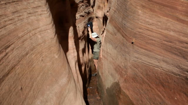 hd video woman navigates zebra slot canyon escalante utah - slot canyon stock videos and b-roll footage