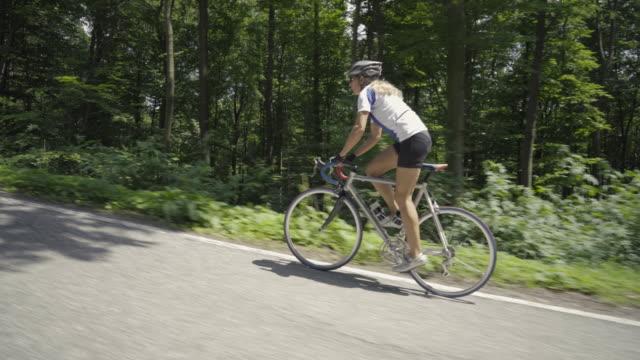 4k video woman on racing bike on street - side view stock videos & royalty-free footage