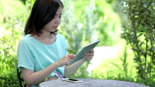 vídeos de stock, filmes e b-roll de vídeo em full hd-mulher jogar tablet no jardim. - jardim de versailles
