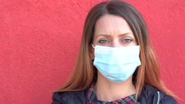 vídeos de stock e filmes b-roll de 4k video woman wearing protective face mask standing in front of a red background - máscara facial