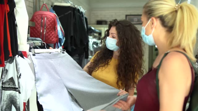 stockvideo's en b-roll-footage met 4k video womеn dragen beschermende masker en winkelen na heropening winkels na covid-19 - heropening