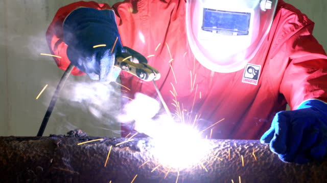 4k video : worker welding the steel part - car plant stock videos & royalty-free footage