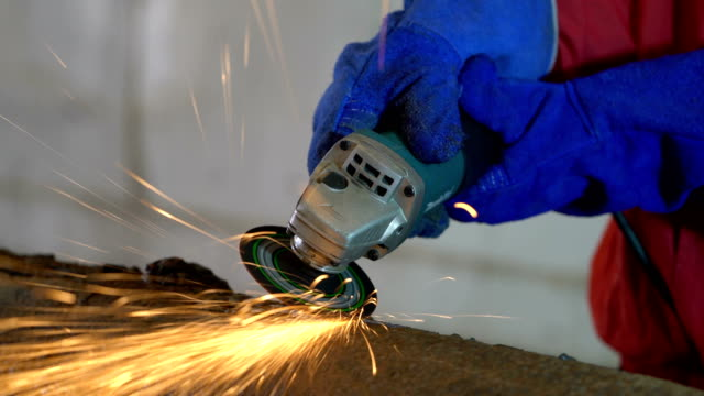 vídeos de stock, filmes e b-roll de 4 k vídeo: trabalhador trabalho em fábrica com moedor - soldar