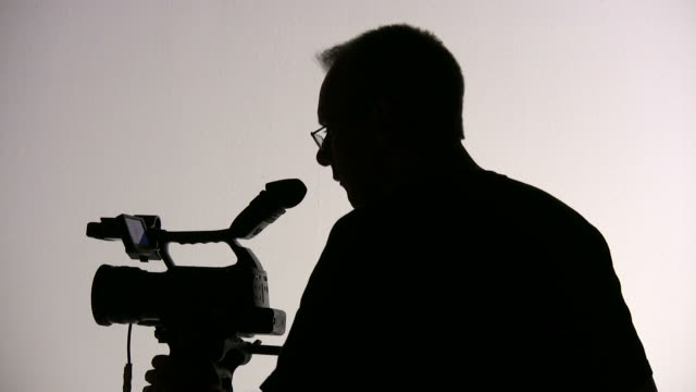 (HD1080i) Videographer Cameraman Adjusts Camera, Directs; Silhouette