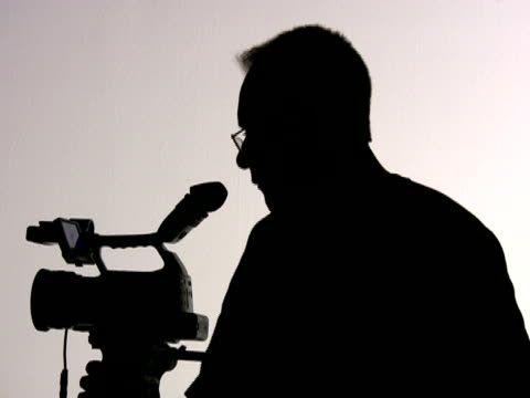 Videographer Cameraman Adjusts Camera, Directs; Silhouette