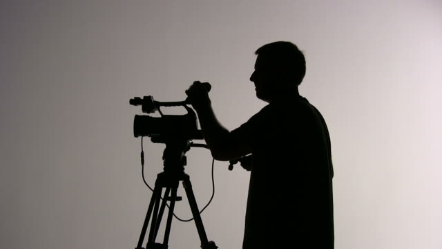 (hd1080i)  videographer cameraman shooting and directing; silhouette - directing stock videos and b-roll footage