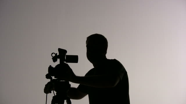 (HD1080i) Videographer Cameraman Shooting, Focus and Panning; Silhouette