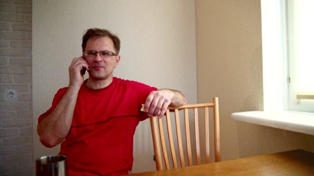 ビデオ-スマート フォンに話してしているハンサムな 50 歳成熟した正男の肖像画。 - 50 54 years点の映像素材/bロール