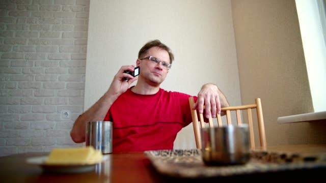 ハンサムな 50 歳中高年正男、ダイニングでお茶を飲んで部屋の videoportrait。 - 50 54 years点の映像素材/bロール