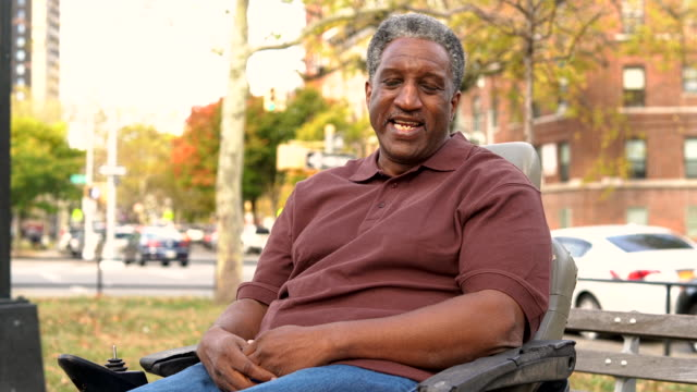 video-portrait of the positive, optimistic disabled black man, paralyzed veteran who sitting in wheelchair - mature adult stock videos & royalty-free footage