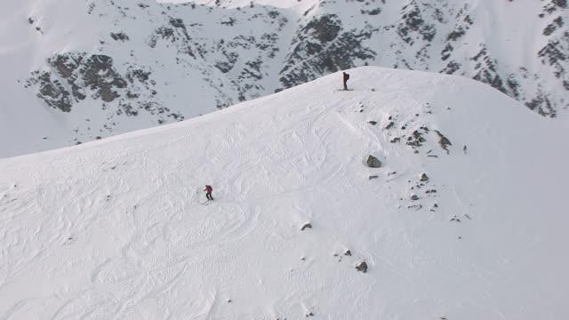 MS AERIAL TS ZO Vie of skier slowly skies down Talkeetna mountains / Alaska, United States