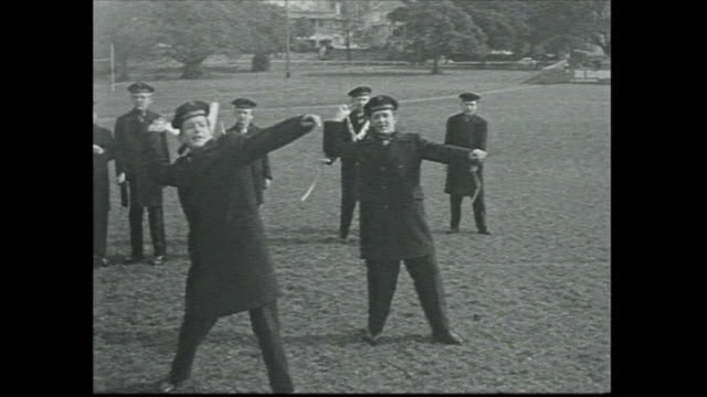 vídeos de stock e filmes b-roll de vienna boys choir members lined up wearing uniforms and beret hats / boys are shown how a boomerang is thrown they then take it in turns to throw one... - bumerangue