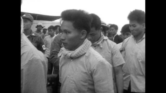 Viet Cong prisoners released at 17th Parallel bridge / injured men with crutches missing hands and legs walk in front of camera / soldiers escort the...