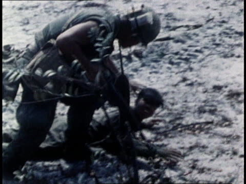 Vietcong POW lying on ground while United States soldiers hold him at gunpoint / Vietnam