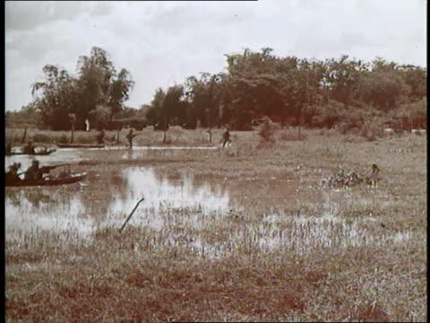 vietcong soldiers run to boats and ride them through marsh - ベトコン点の映像素材/bロール