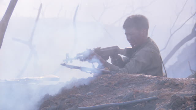 vietcong soldiers shoot their rifles from behind a trench. - vietnam war stock videos & royalty-free footage