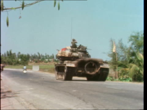 report from tay ninh:; vietnam: tay ninh area: ext tank and troops: tank by tree by road: tank gun points r-.l: fv tank pan road: bv soldier with... - ベトナム戦争点の映像素材/bロール