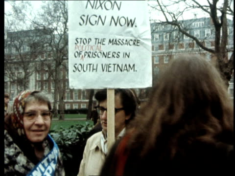 vietnam england gv embassy slogan on l 'nixon sign now' track demos slogans in single file opposite embassy on pavement ekt 16mm itn 32secs 20ft - vietnam war stock videos & royalty-free footage