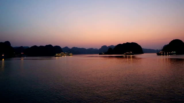 vietnam halong bay landscape at dusk hd pan left with many moored tourist boats - halong bay stock videos and b-roll footage